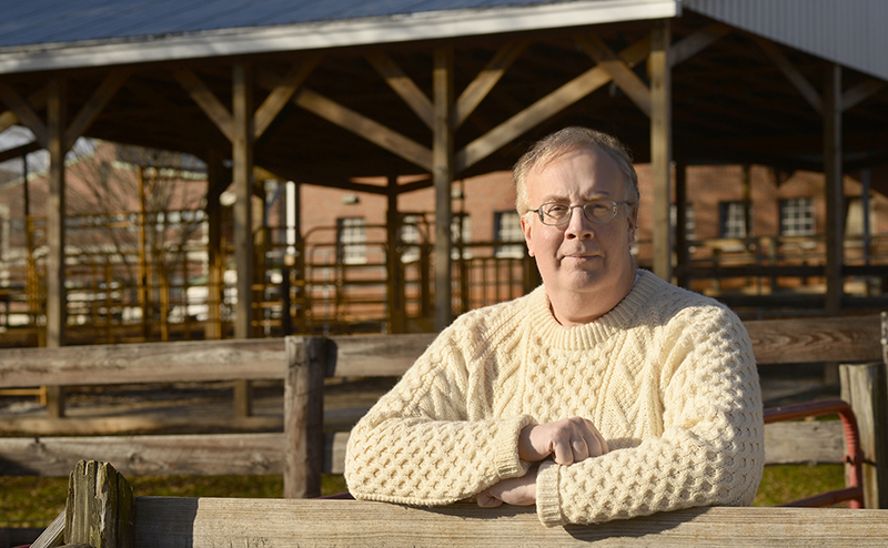 Dr. David Dorman stands in front of barn.