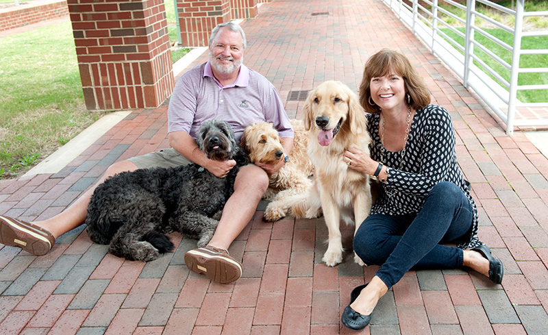 Couple sits with three dogs on brick walkway