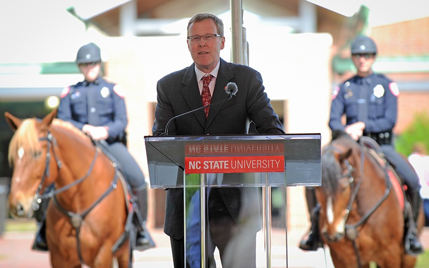Dean Lunn at podium, two mounted police officers stand watch behind.