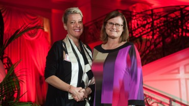 Two women shaking hands in front of red background