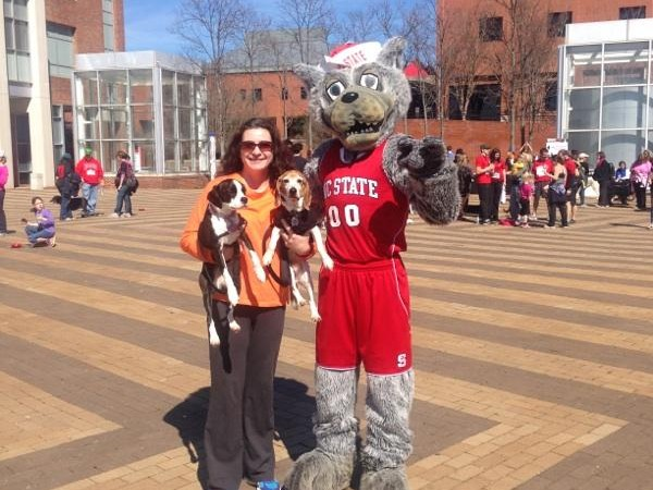Wolf mascots stands with woman and dog