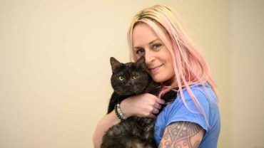 Woman with blonde hair holding black cat